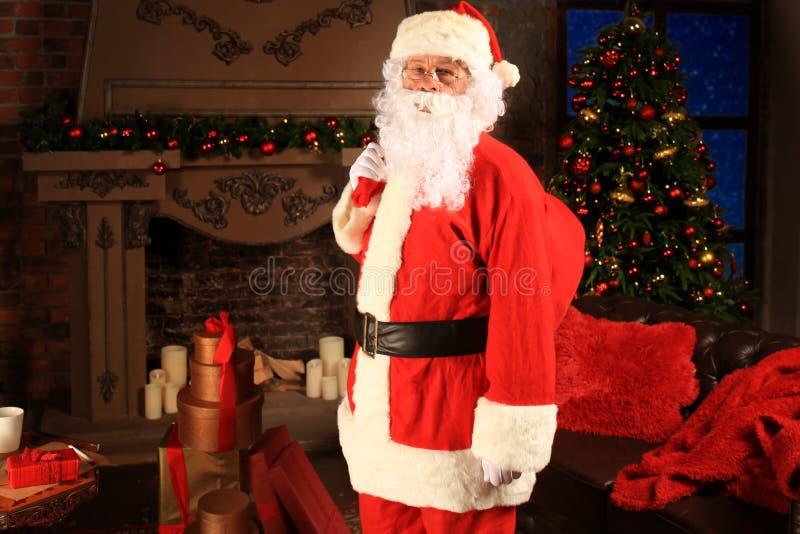Santa Claus-holdings dragende zak met giften voor jonge geitjes stock foto's
