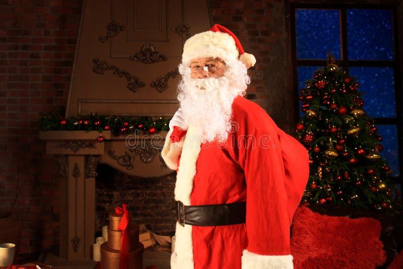 Santa Claus-holdings dragende zak met giften voor jonge geitjes royalty-vrije stock foto