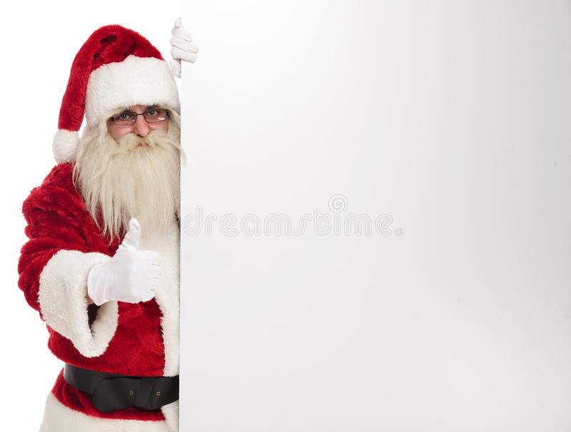 Santa claus holds white empty board and makes ok sign royalty free stock images