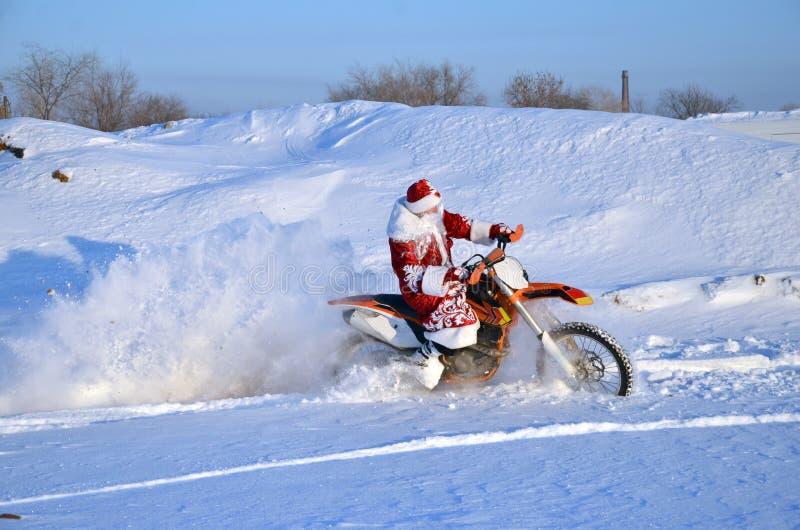 Santa Claus a horcajadas en la bici del motocrós imagen de archivo