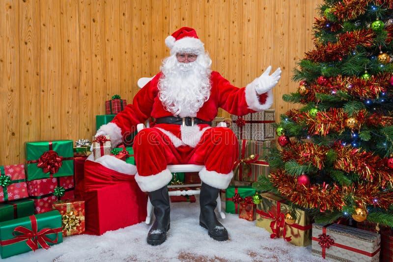 Santa Claus i en grotta som ut räcker gåvor royaltyfria foton