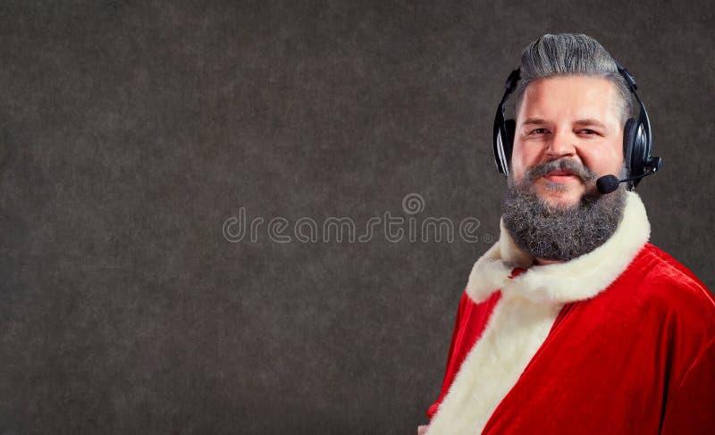 Santa Claus i en operatör för hörlurar med mikrofonappellmitt arkivbilder