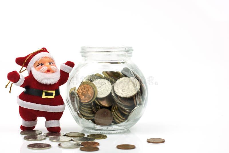 Santa Claus i pieniądze monety w szkle isoalted na białym backgroun obraz royalty free