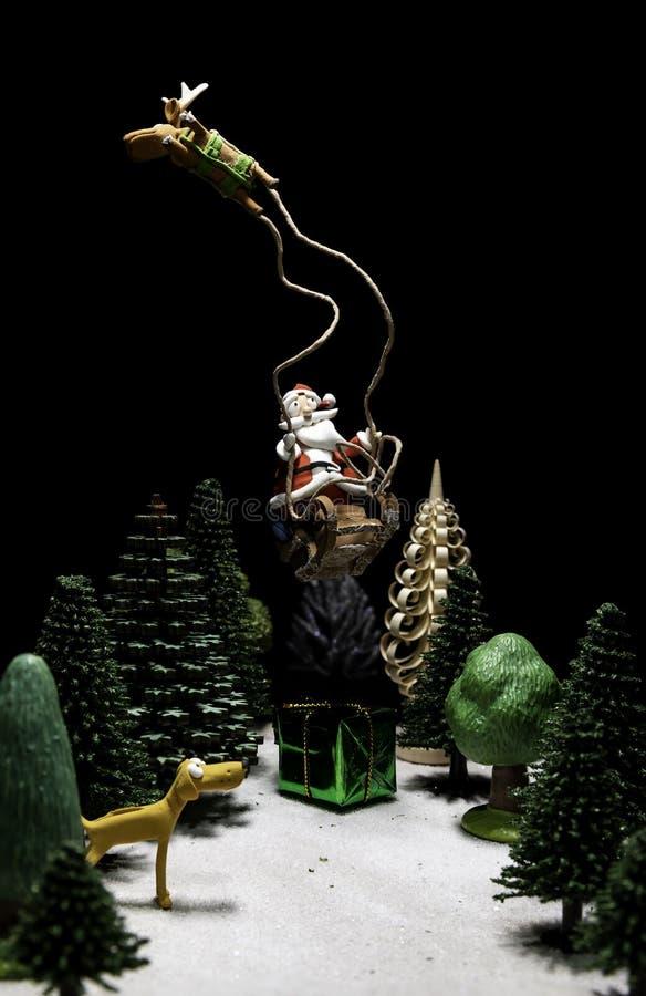 Santa Claus i släde med ett renflyg över den gröna gåvaasken och guling arkivfoton