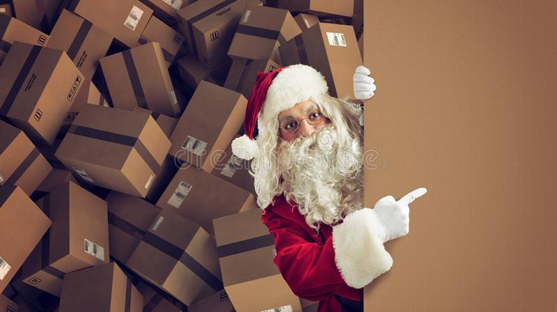 Santa Claus indicates a space for the Christimas present, with ready packages on background. Santa Claus indicates a blank space for the Christmas present, with royalty free stock photography