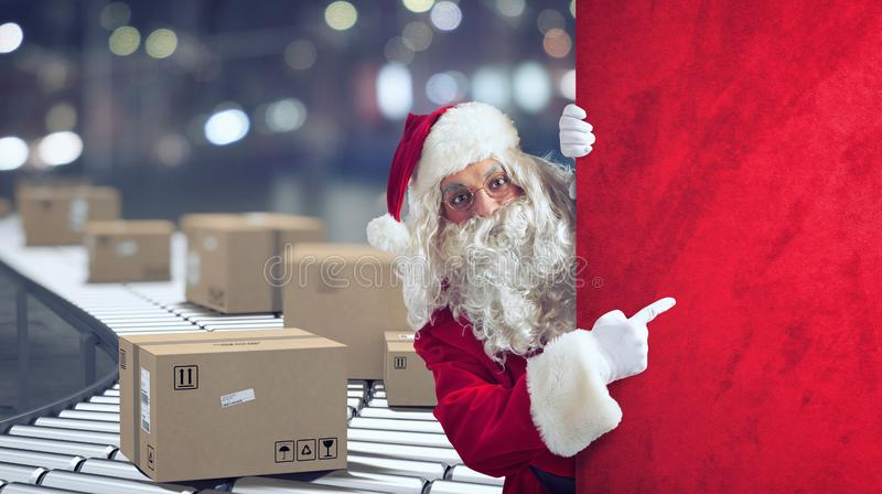 Santa Claus indicates a space for the Christimas present, with ready packages on background. Santa Claus indicates a blank space for the Christmas present, with stock photos