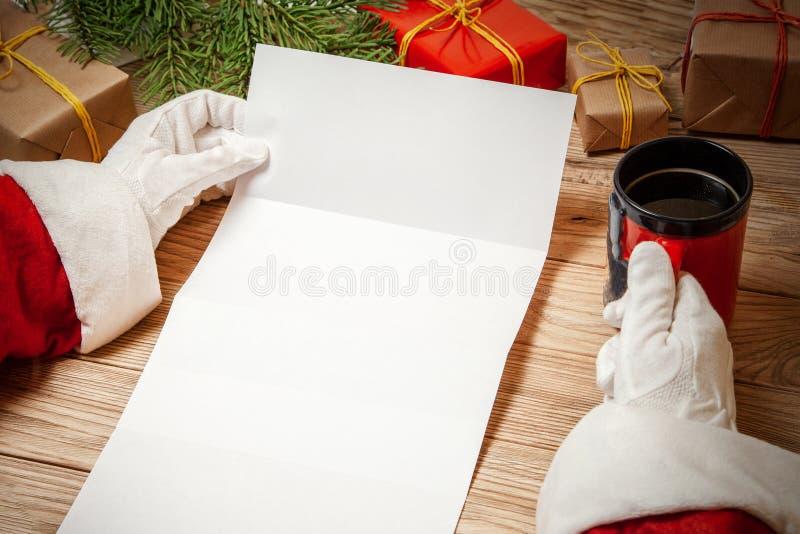 Santa Claus innehavbokstav på trätabellen med gåvaaskar och julgran och kopp av varmt kaffe eller te modellmellanrum royaltyfri bild
