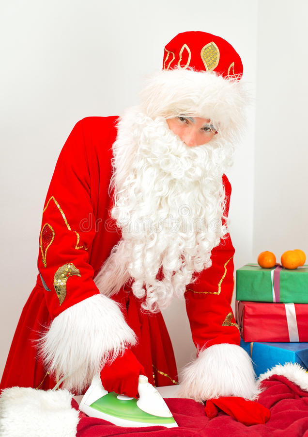 Santa Claus ironing clothes. stock photo