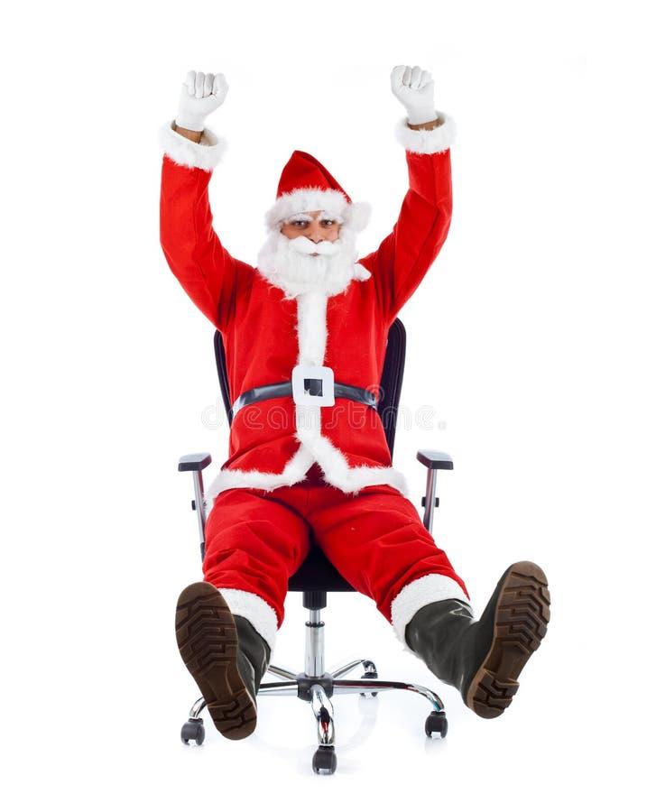 Santa Claus joven que se sienta en una silla de la oficina. fotos de archivo