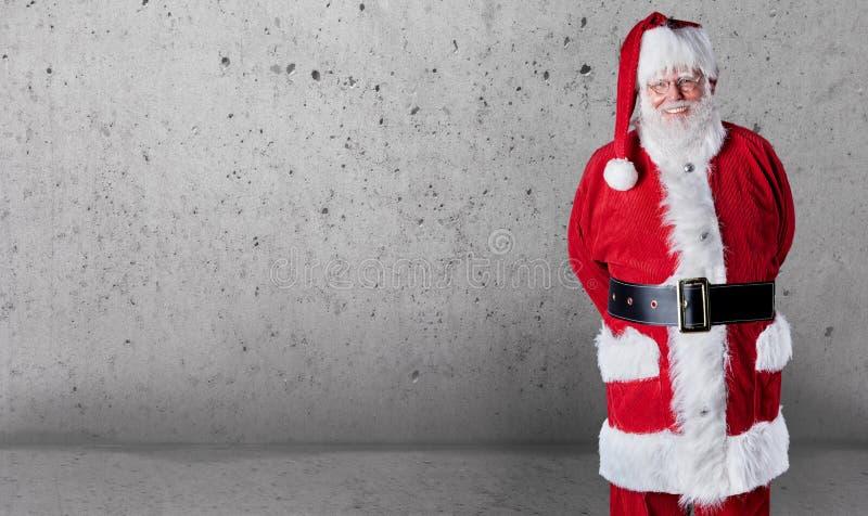 Santa Claus jovial feliz com espaço da cópia sobre um fundo textured cinzento da parede para desejar-lhe o Feliz Natal fotografia de stock