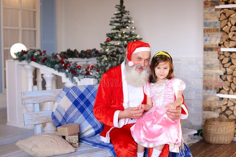 Santa Claus joyeuse parlant avec la petite princesse photographie stock