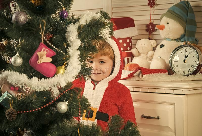 Santa claus kid decorating Christmas tree.. royalty free stock image