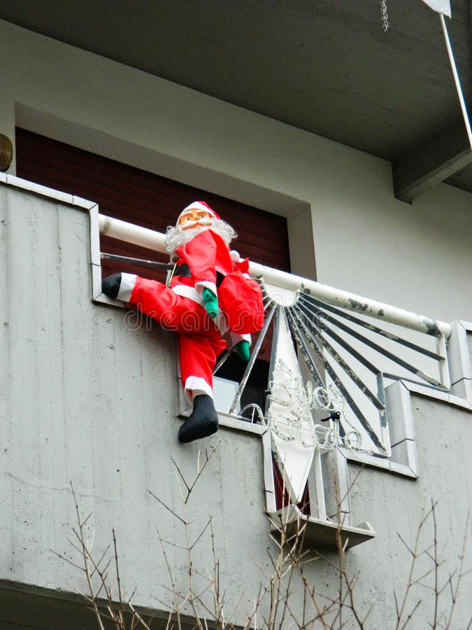 Santa Claus klättring ut ur fönstret på trappan ` S för nytt år och jul arkivfoto