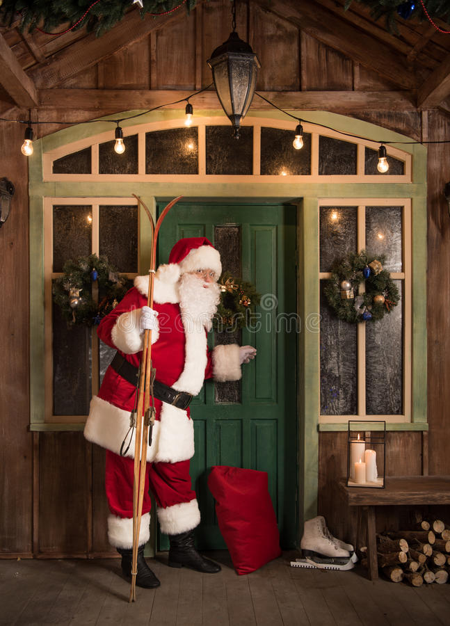 Santa Claus knocking in door. Santa Claus standing with skis and knocking in door stock image