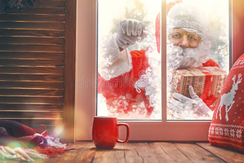 Santa Claus is knocking at window. Merry Christmas! Santa Claus is knocking at window. Room decorated for holidays. View indoors home stock photography