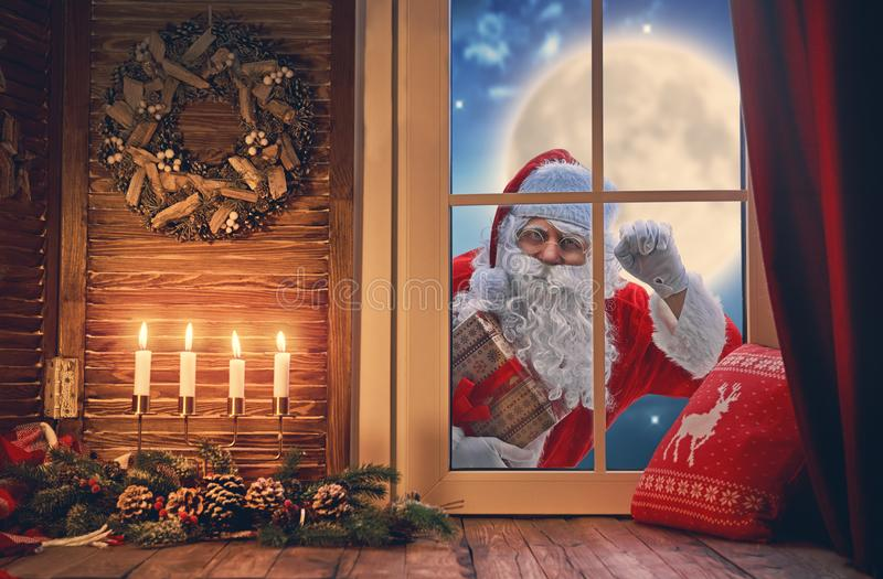 Santa Claus is knocking at window. Merry Christmas! Santa Claus is knocking at window. Room decorated for holidays. View indoors home royalty free stock photo