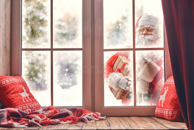 Santa Claus is knocking at window. Merry Christmas! Santa Claus is knocking at window. Room decorated for holidays. View indoors home royalty free stock images