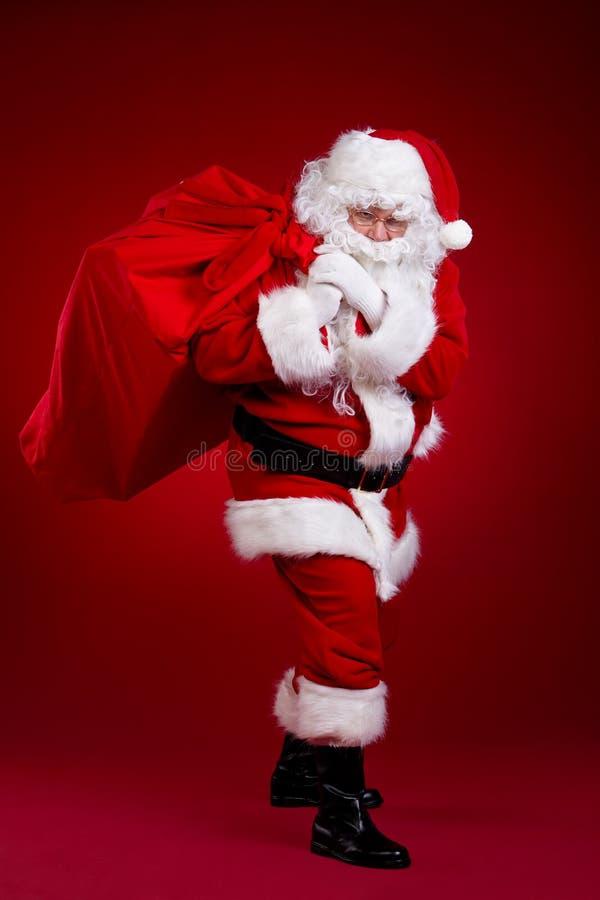 Santa Claus kommt mit einer großen Tasche von Geschenken In voller Länge Portrait lizenzfreie stockfotografie
