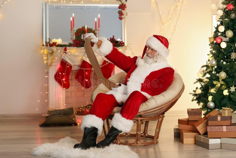 Santa Claus läsningönskelista i rum som dekoreras för jul arkivfoto