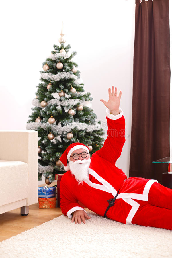Santa Claus Laying In Front Of Christmas Tree Royalty Free Stock Photo