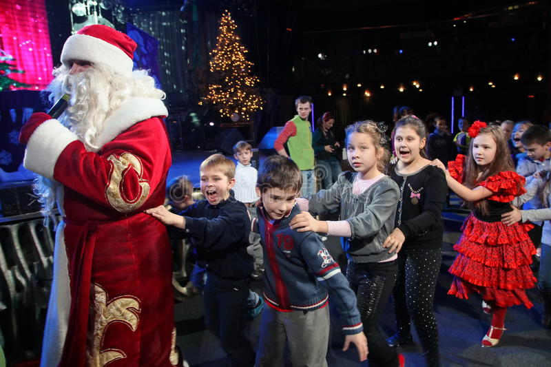 Santa Claus leads the children a cheerful holiday dances. Christmas night. Santa Claus on stage. royalty free stock photo