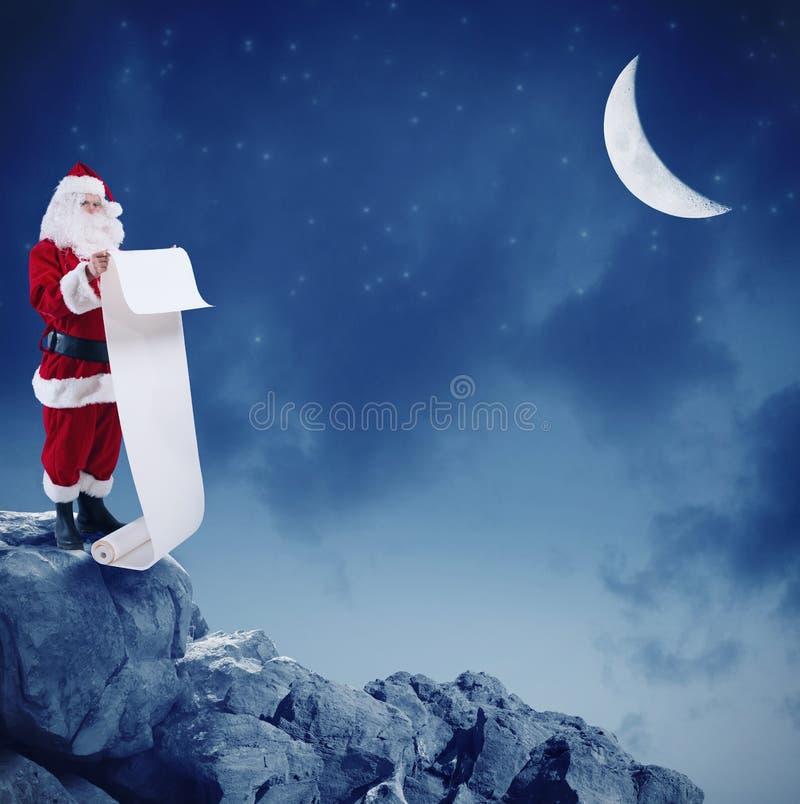 Santa Claus legge la lista dei regali sul picco di una montagna sotto la luna immagine stock