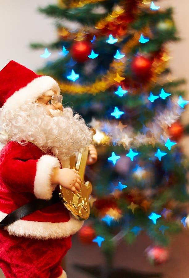 Santa Claus leksak som spelar gitarren arkivfoto