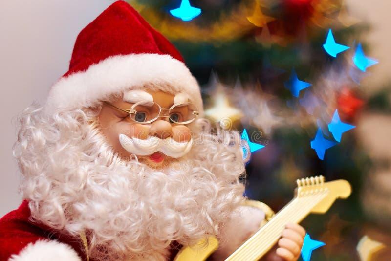 Santa Claus leksak som spelar gitarren arkivbilder