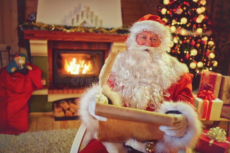 Santa Claus-Lesekinderwünsche für Weihnachten lizenzfreies stockfoto