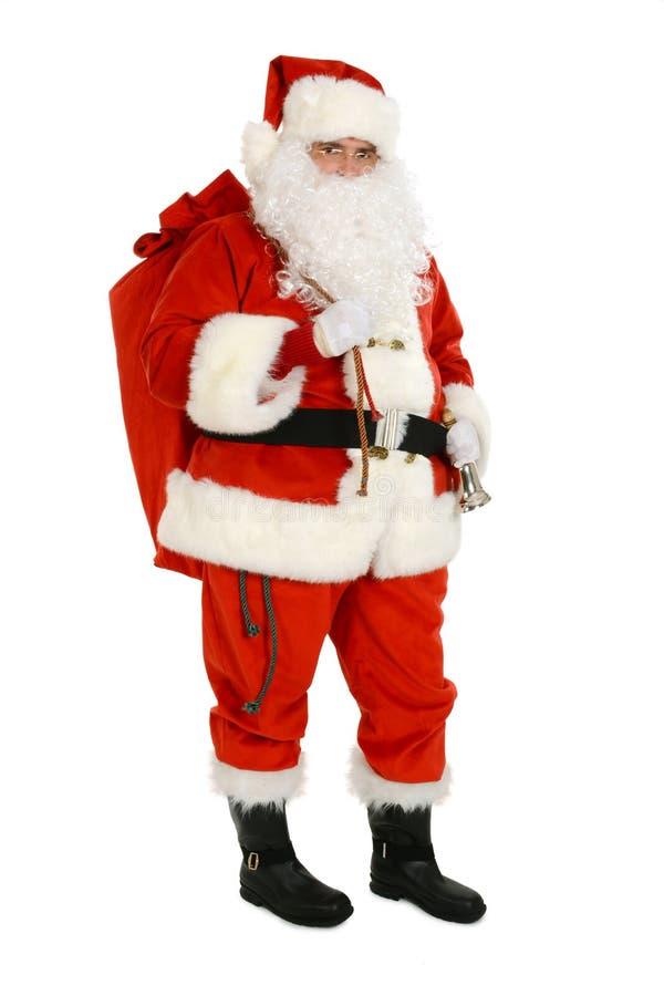Santa Claus leva o saco completamente de presentes no seu para trás foto de stock royalty free