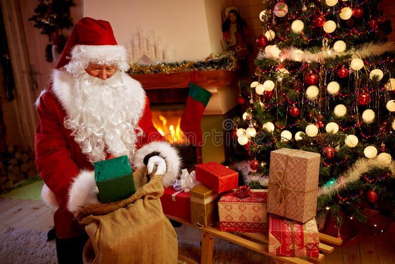 Santa Claus levererar gåvor i hem- nästa julgran arkivbilder