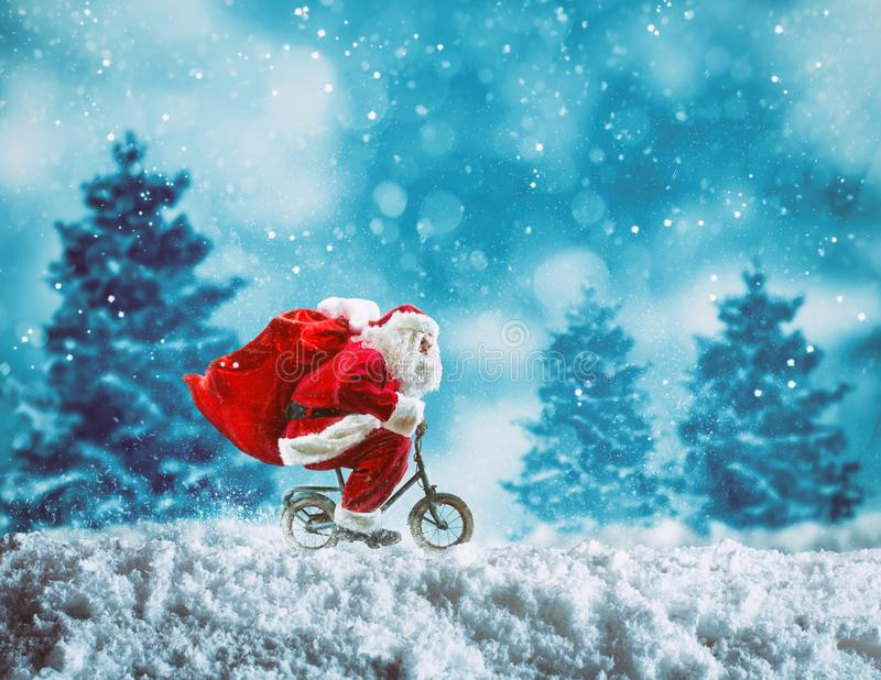 Santa Claus on a little bike on a winter landscape under the snow stock images