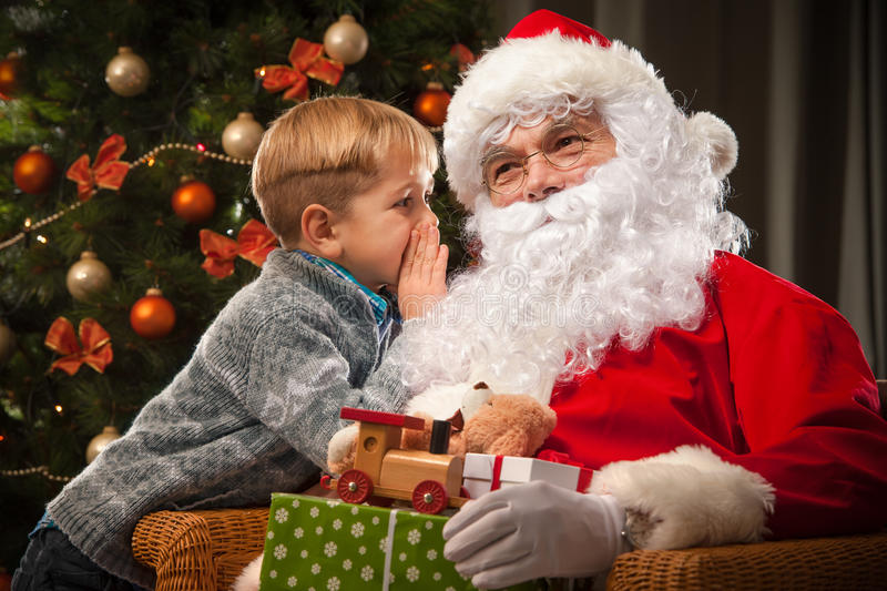 Santa Claus and a little boy. Boy tells wishes in front of Christmas Tree stock photo