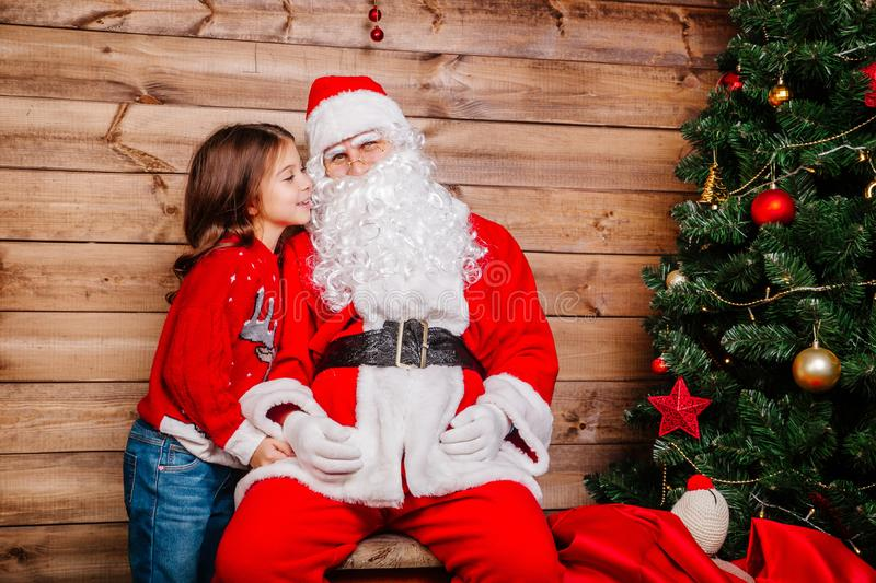 Santa Claus and Little girl. Girl telling wish in Santa Claus`s ear in front of Christmas Tree royalty free stock photography