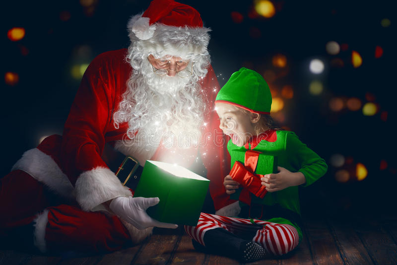 Santa Claus and little girl. Cute little girl and Santa Claus opening a magic gift box royalty free stock image
