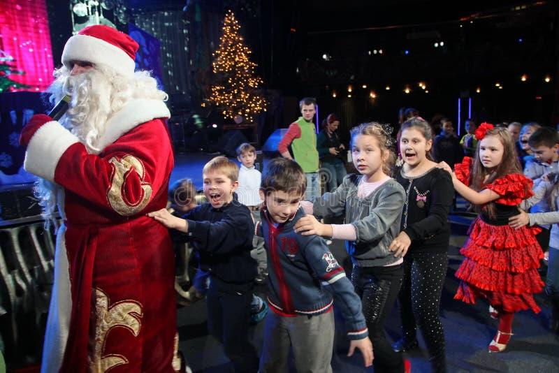 Santa Claus lleva a los niños que un día de fiesta alegre baila Noche de la Navidad Santa Claus en etapa foto de archivo libre de regalías