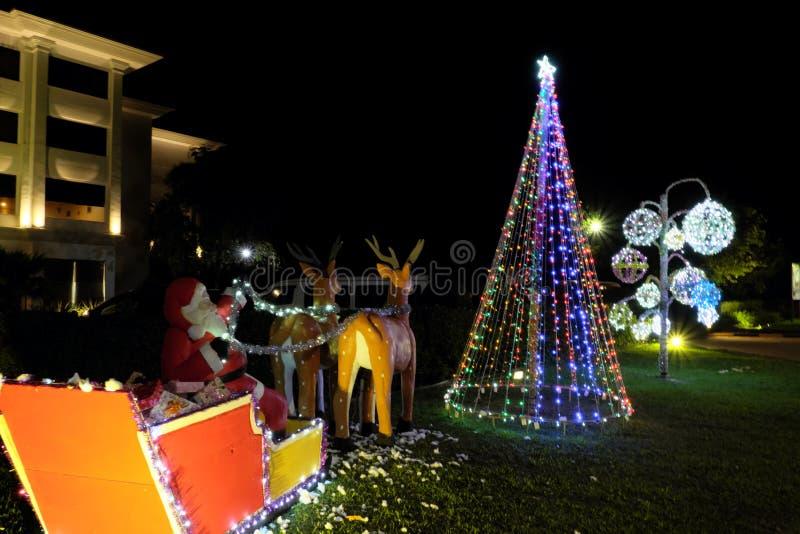 Santa Claus lleva los regalos en un trineo dibujado por el reno Decoraci?n del A?o Nuevo Iluminaci?n festiva de la calle fotos de archivo