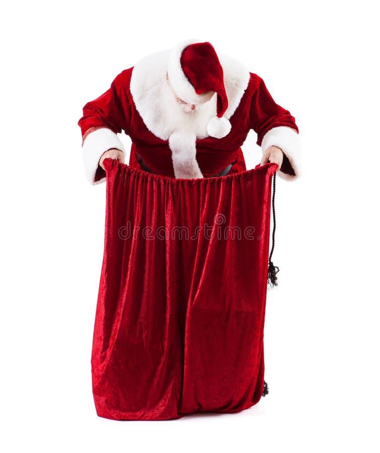 Santa Claus Looks Down Into Bag van Giften stock foto