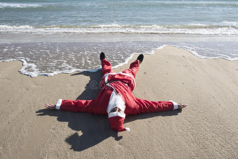 Santa claus lying on the sand of a beach. Santa claus lying face up on the sand of a beach, with the sea in the background royalty free stock photos