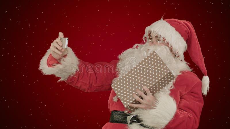 Santa Claus maakt selfie, houdend een groot heden op rode achtergrond met sneeuw stock fotografie