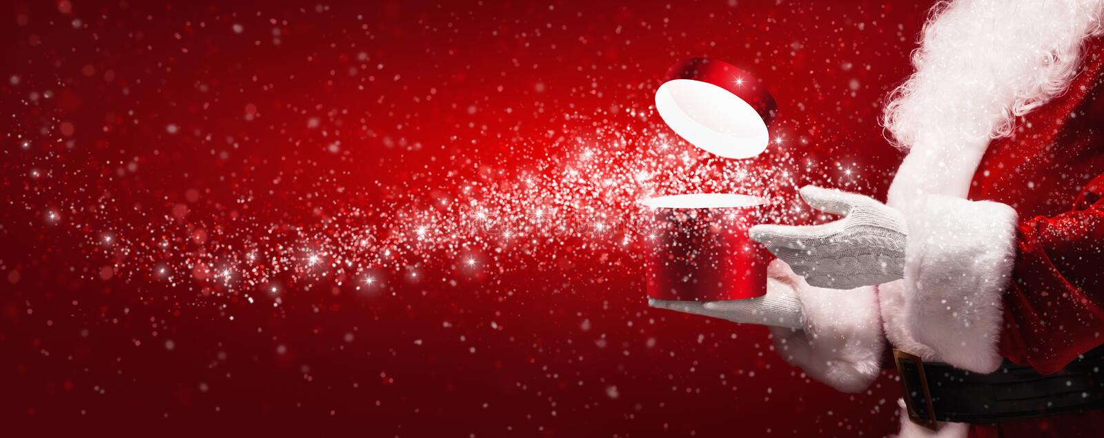 Santa Claus with magic box. And snow on red background stock photos