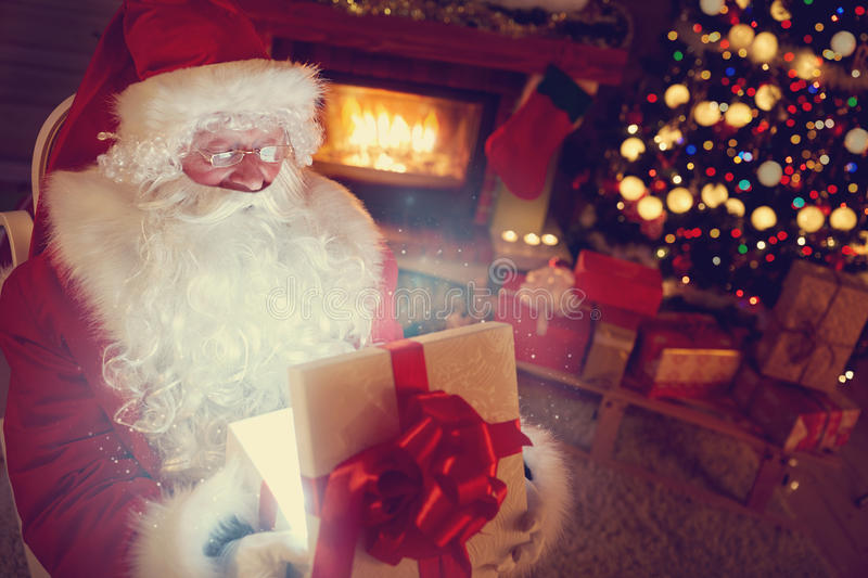 Santa Claus with magic gift. Santa Claus opening magic gift in home next Christmas tree royalty free stock photography