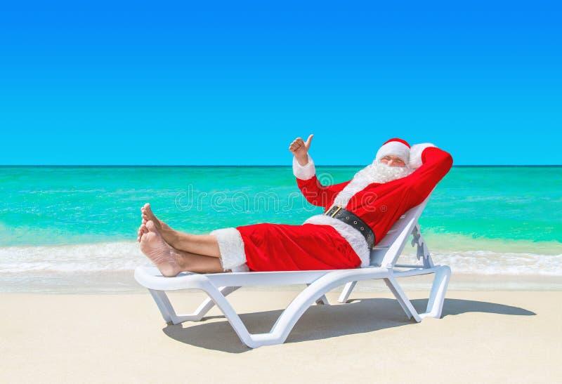 Santa Claus manosea con los dedos encima de gesticular en sunlounger en la playa tropical fotos de archivo libres de regalías