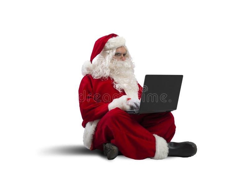 Santa Claus med bärbara datorn arkivbilder