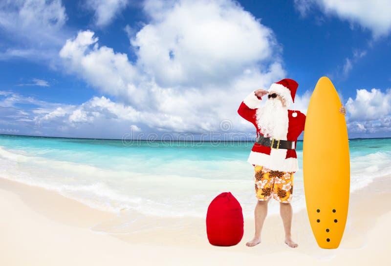 Santa Claus med bränningbrädet på stranden fotografering för bildbyråer