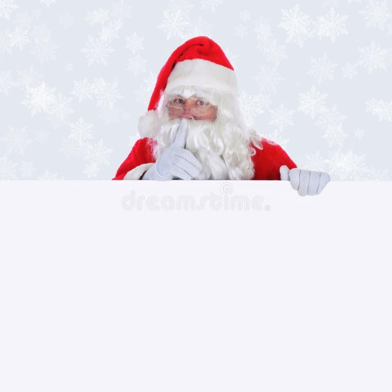 Santa Claus med det tomma tecknet som gör shhh tecknet med en ljussilverbakgrund med snöflingor arkivfoto