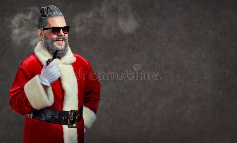 Santa Claus med en frisyr och en cigarr lanserar en rök royaltyfria foton