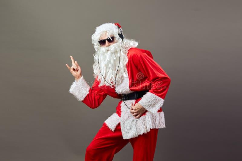 Santa Claus med ett långt vitt skägg i solglasögon och hörlurar visar att vagga för att sjunga på den gråa bakgrunden arkivbilder