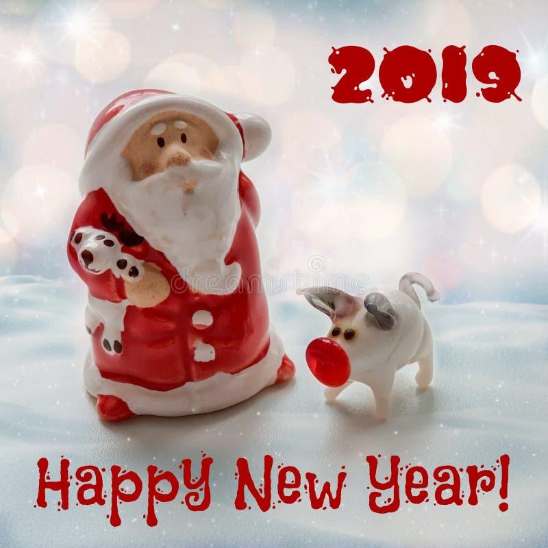 Santa Claus med ett litet svin - ett symbol av 2019 med en lyckönsknings- inskrift royaltyfria bilder