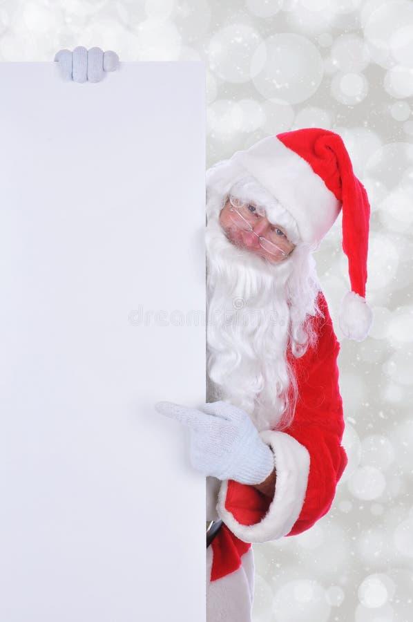 Santa Claus med ett tomt tecken med kopieringsutrymme royaltyfri fotografi